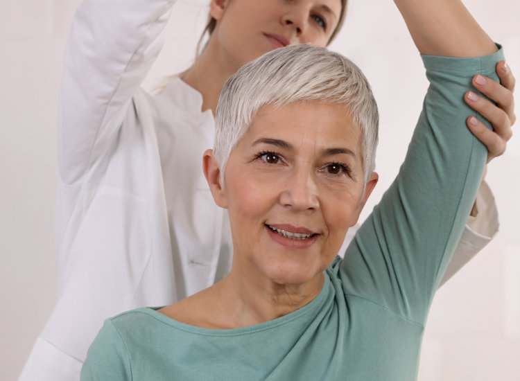 Osteopath Stretching Woman's Shoulder
